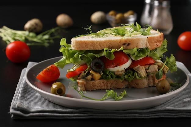 Sanduíche com frango, tomate cereja, ovos de codorna, azeitonas e microgreens contra uma mesa escura
