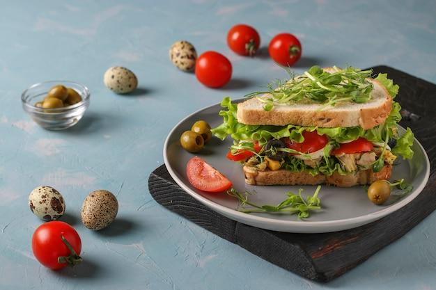 Sanduíche com frango, tomate cereja, ovos de codorna e microgreens contra um fundo azul claro