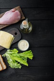 Sanduíche com ingredientes frescos, em fundo preto de madeira, vista superior com espaço de cópia para o texto