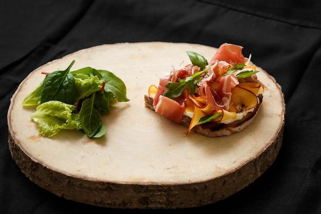 Sanduíche com jamon e alface em uma bandeja de madeira