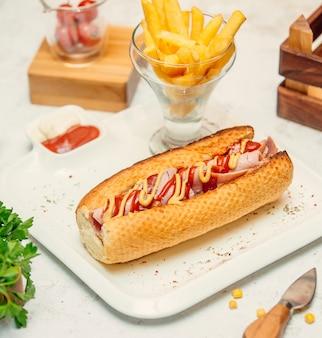 Sanduíche com linguiça com molho e batatas fritas