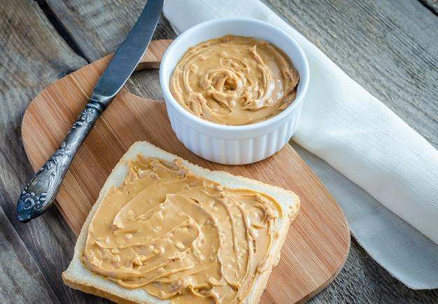 Sanduíche com manteiga de amendoim na placa de madeira