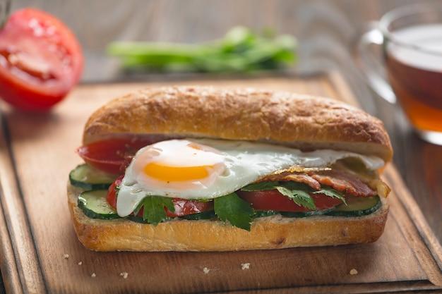 Sanduíche com ovo, bacon, legumes e ervas.