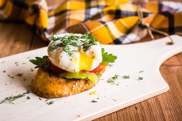 Sanduíche com ovo escalfado e tomate em uma placa de corte
