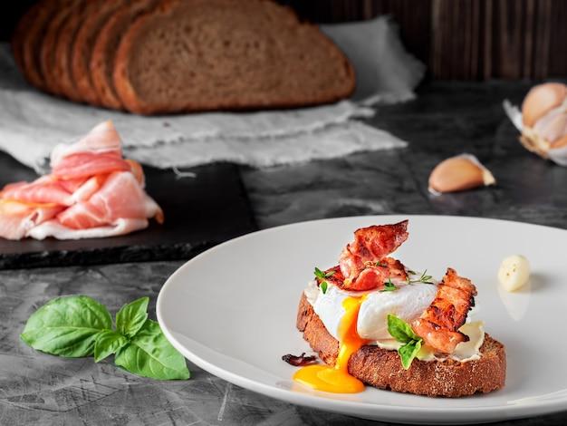 Sanduíche com ovo escalfado, presunto frito e cream cheese, guarnecido com folhas de manjericão