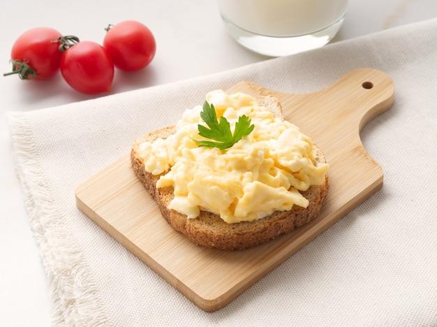 Sanduíche com ovos mexidos fritos na placa de corte de madeira, vista lateral.