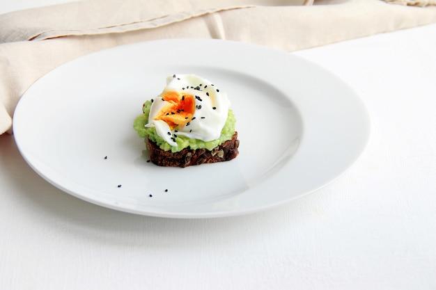 Sanduíche com pão preto, abacate e ovo escalfado em um prato branco