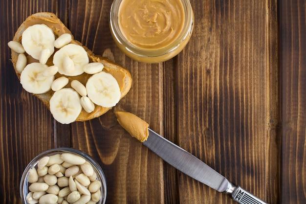 Sanduíche com pasta de amendoim e banana no fundo de madeira marrom. vista superior. copie o espaço.