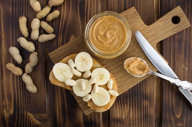 Sanduíche com pasta de amendoim e banana numa tábua no fundo de madeira marrom. vista superior.