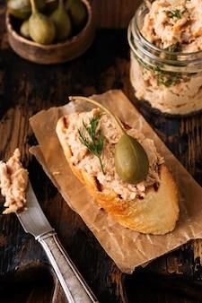 Sanduíche com patê de frango com alcaparra em uma placa velha escura.