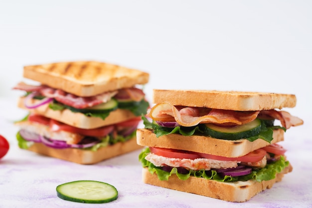 Sanduíche com peito de frango, bacon, tomate, pepino e ervas