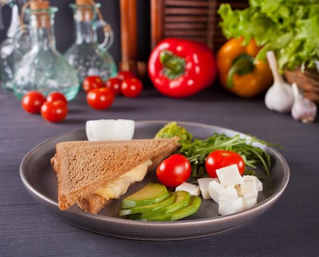 Sanduíche com peito de peru, queijo, alface, rúcula, tomate, queijo feta, abacate e cebola em um prato