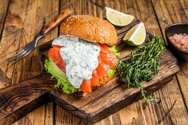 Sanduíche com peixe salgado, salmão, abacate, pão de hambúrguer, molho de mostarda e salada de iceberg