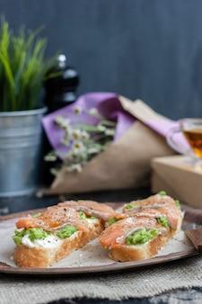 Sanduíche com peixe vermelho, queijo branco e abacate, flores