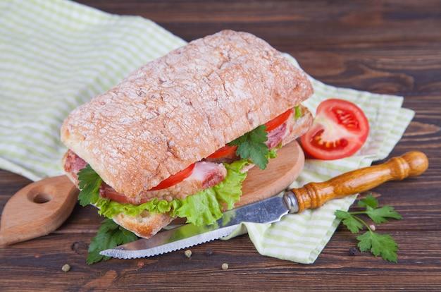 Sanduíche com presunto e legumes em um fundo escuro de madeira.
