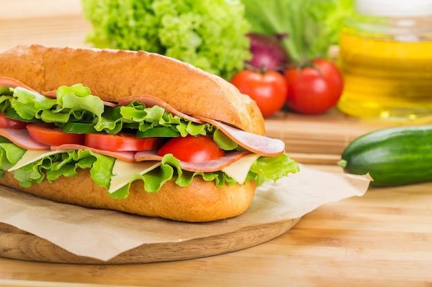 Sanduíche com presunto e legumes na tábua de madeira