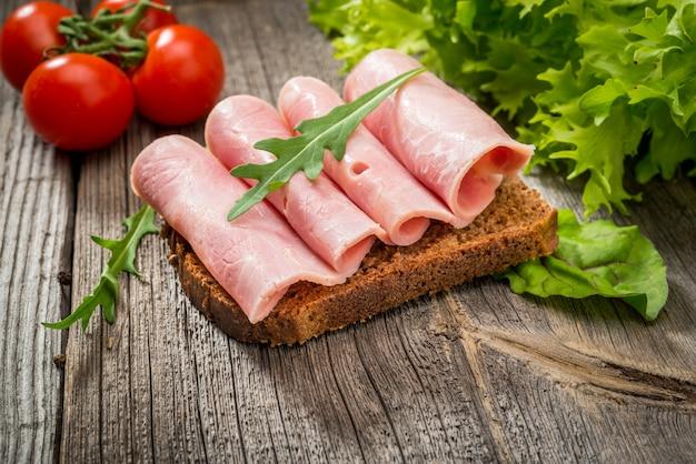 Sanduíche com presunto e legumes. produtos orgânicos em uma mesa de madeira