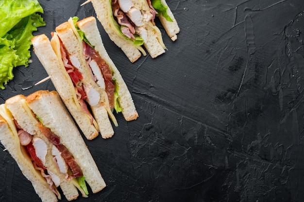 Sanduíche com presunto, queijo, tomate, alface, carne de frango e pão torrado, em fundo preto, vista superior com espaço de cópia para o texto