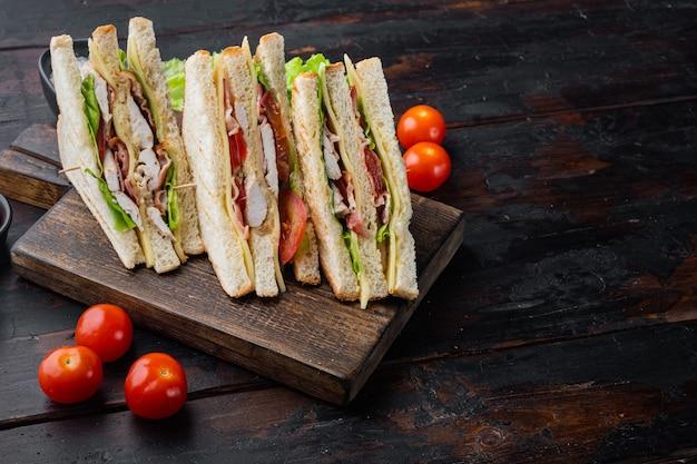Sanduíche com presunto, queijo, tomate, alface, carne de frango e pão torrado, na velha mesa de madeira com espaço de cópia para o texto