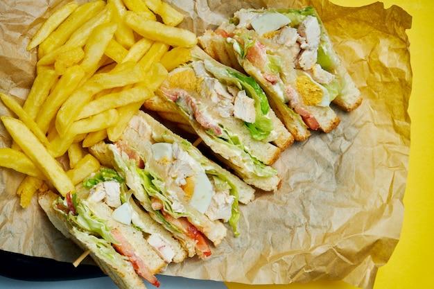 Sanduíche com presunto, tomate, pepino em conserva, ovo, queijo e alface em uma bandeja de madeira. fechar-se. saborosa comida rápida.
