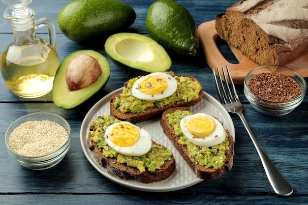 Sanduíche com purê de abacate e ovo em um prato e ingredientes para cozinhar em uma mesa de madeira azul.