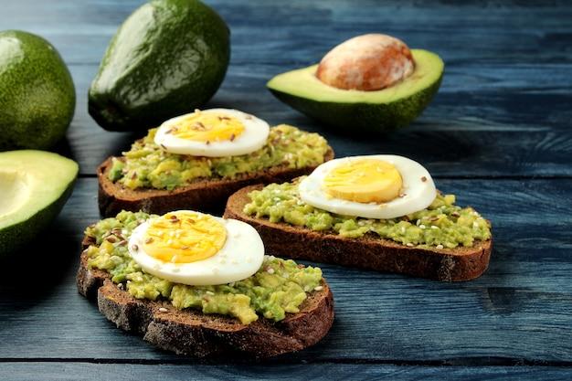 Sanduíche com purê de abacate e ovo em uma mesa de madeira azul. abacate fresco