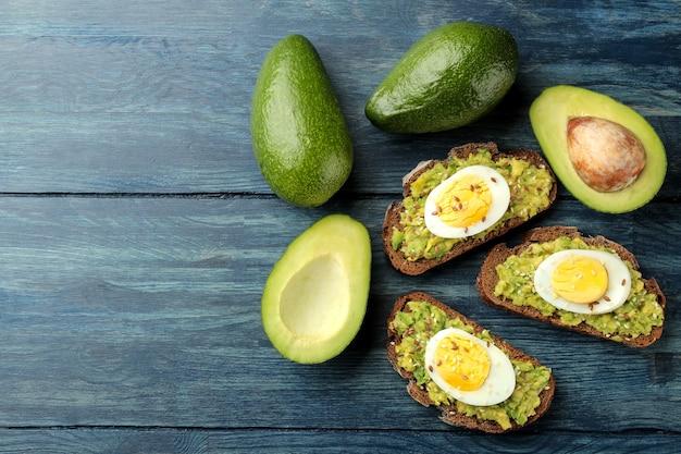 Sanduíche com purê de abacate e ovo em uma mesa de madeira azul com espaço para texto. vista de cima