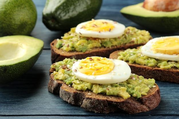 Sanduíche com purê de abacate e ovo em uma mesa de madeira azul. fechar-se