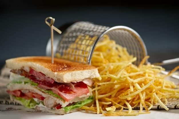 Sanduíche com queijo, bacon, tomate, salada verde e vermelha e batata frita