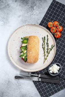 Sanduíche com queijo camembert fresco, marmelada de pêra, ricota e rúcula. fundo cinza. vista do topo