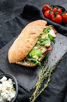 Sanduíche com queijo camembert fresco, marmelada de pêra, ricota e rúcula. fundo preto. vista do topo