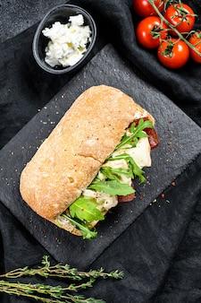 Sanduíche com queijo camembert fresco, marmelada de pêra, ricota e rúcula. superfície preta. vista do topo