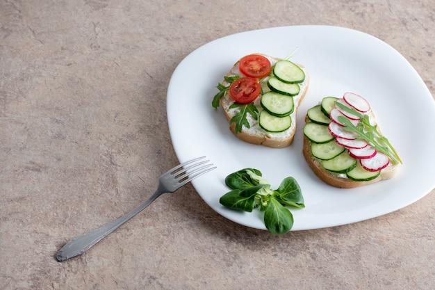 Sanduíche com queijo cottage, pepino e tomate cereja e rabanete em um prato branco sobre a mesa. prato com um garfo na mesa com um prato branco com salada de legumes.