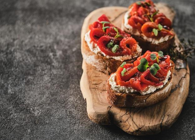 Sanduíche com queijo macio e pimentão vermelho assado em uma placa de madeira. antipasti de bruschetta italiana. copyspace.