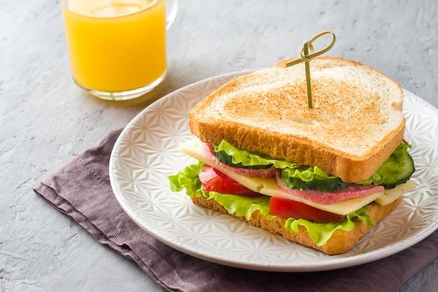 Sanduíche com queijo, presunto e legumes frescos em uma placa.
