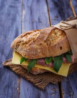 Sanduíche com queijo, rúcula, presunto.