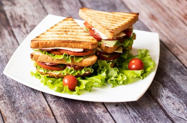 Sanduíche com queijo, tomate, pepino, salsicha e salada na madeira