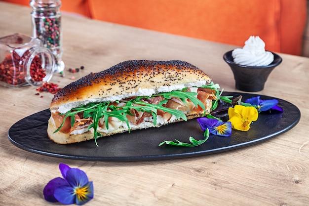 Sanduíche com rúcula, creme de queijo e presunto na placa de pedra escura. sanduíche submarino fresco com espaço de cópia. fast-food, lanche. sanduíche saudável