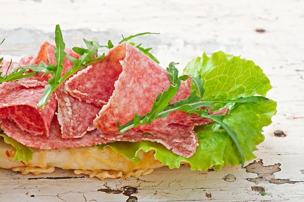 Sanduíche com salame, alface, tomate e rúcula