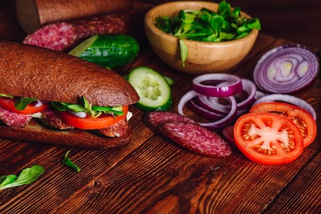 Sanduíche com salame e legumes. ingredientes fatiados