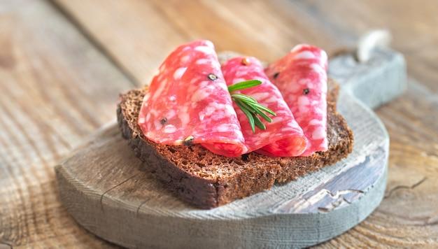 Sanduíche com salame na placa de madeira