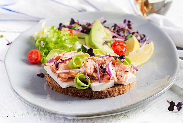 Sanduíche com salmão assado, queijo feta, abacate e microgreens