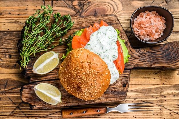 Sanduíche com salmão de peixe salgado, abacate, pão de hambúrguer, molho de mostarda e salada de iceberg.