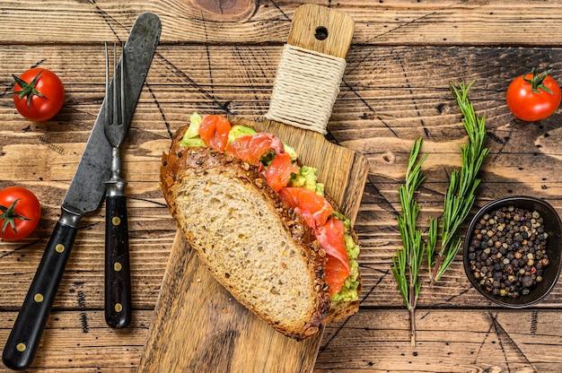 Sanduíche com salmão defumado, abacate e ovo. fundo de madeira. vista do topo.