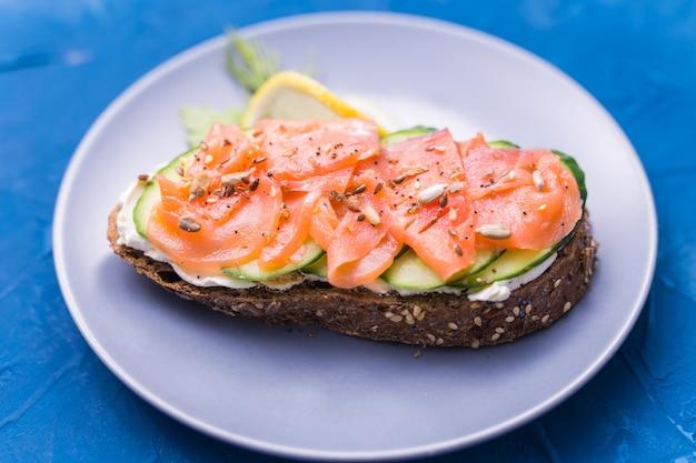 Sanduíche com salmão defumado e pepino. conceito de nutrição saudável.