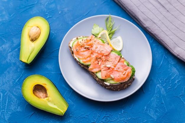 Sanduíche com salmão defumado e pepino em fundo azul com abacate, vista superior. conceito para