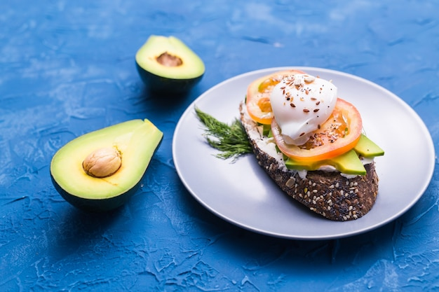 Sanduíche com salmão defumado, ovo e abacate na superfície azul, vista superior. conceito de nutrição saudável.