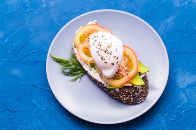 Sanduíche com salmão defumado, ovo e abacate sobre fundo azul, vista superior. conceito de saúde