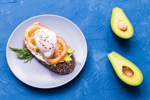 Sanduíche com salmão defumado, ovo e abacate sobre fundo azul, vista superior.