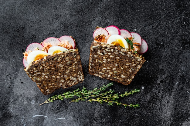 Sanduíche com salmão defumado quente e pão integral. truta. superfície preta, vista superior.
